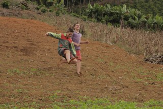 Foto de dois garotos correndo, eles descem um morro.