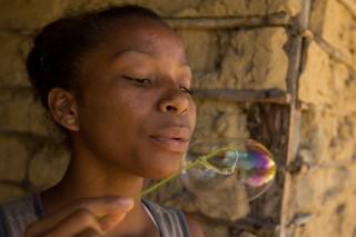 Foto de uma garota que segura uma folha que em sua ponta esta dobrada, formando um aro, ela utiliza deste aro para assoprar e fazer bolinhas de sabão.