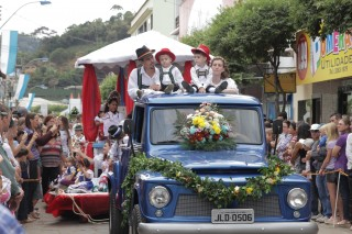 Foto de um desfile onde, pessoas estão em cima de uma caminhonete azul.