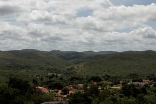 Foto ilustrando um vale com várias casas no centro do vale, ao fundo várias montanhas.