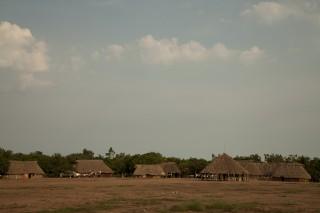Foto ilustrando uma pequena vila com casa com teto de palha e estrutura de madeira.