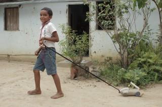 Foto com um garoto puxando um carrinho feito de uma garrafa de alvejante, o garoto puxa com uma corda amarrada.