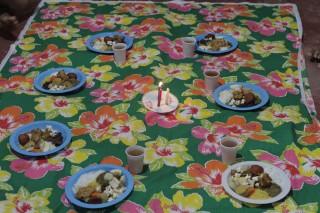 Foto de um pano multicolorido estendido, que em cima dele tem vários pratos plástico com comida dentro e um copo de plástico com suco ao lado deles, os pratos formam um círculo, no centro tem um prato com três velas acessas.