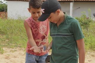 Foto com duas crianças brincando um peão, as duas crianças estão com a mão direita estendida, um garoto de blusa vermelha e outro de boné preto, o garoto de boné preso segura um peão que gira em sua mão.
