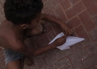 Foto de um garoto negro, abaixado ele dobra uma pipa com uma folha sulfite.
