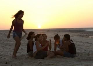 Foto ilustrando garotas sentadas em um circulo enquanto uma esta correndo em volta com um chinelo na mão ao por do sol.