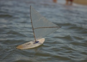 Foto de um barquinho a vela feito com plástico linhas e madeira em um rio.