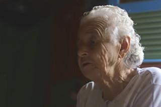 Foto de uma senhora falando enquanto olha em direção ao vazio.