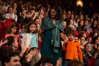 Foto de um salão cheio de pessoas sentadas observando uma mulher descer as escadas, de mãos dadas a uma menina e um menino.