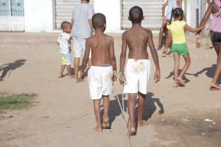 Foto de dois garotos negros sem camisa de bermuda branca estão amarrados em seus pulsos uma corda, ambos estão andando.