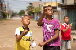 Foto com Três garotos soltando pipa.