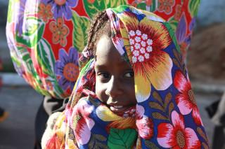 Imagem de uma garota envolvida por um lenço todo florido
