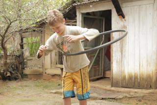 Foto de um garoto brincando com um bambolê.