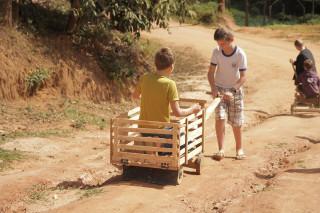 Foto de dois garotos brincando com um carrinho de madeira , onde um dos garotos está dentro do carrinho e o outro está do lado de fora puxando o carrinho de madeira.