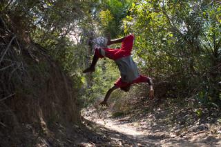 Foto de um garoto dando um salto mortal.