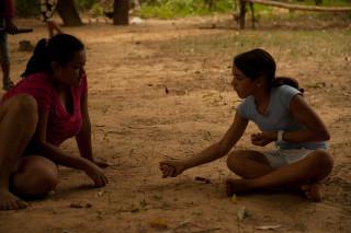 Foto de uma interação entre duas garotas sentadas no chão
