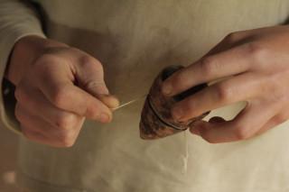 Foto de uma pessoa dando corda em um pião de madeira.