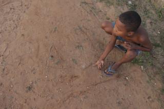 Imagem de um garoto ao chão brincando com bolinhas de gude.
