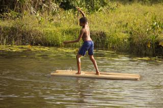 Foto de um garoto brincando sob uma madeira em um rio.