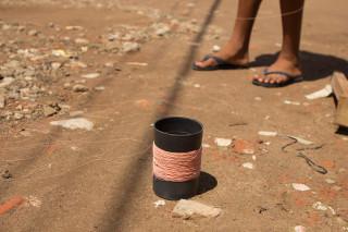 Foto de um carretel de linha de pipa e os pés de uma criança.
