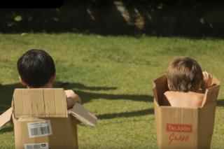 foto de duas crianças de costas, brincado dentro de caixas de papelão, onde o garoto da direita se inclina dentro de sua caixa.