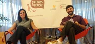 Foto com duas pessoas sentadas, uma mulher e ao seu lado esquerdo um homem de barba, ambos estão de pernas cruzadas e sorrindo.