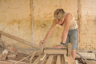 Foto de um garoto, inclinado encaixa a roda de um carrinho de madeira feito a mão.
