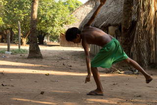 Foto de um garoto sem camisa e de bermuda verde, curvado arremessa um peão no chão de terra.