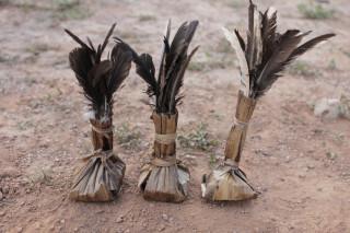 Foto de três petecas feitas com palha e pena ambas estão sobre um solo de terra.