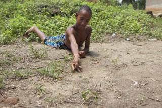 Foto de um garoto negro deita em um chão de terra, com seu braço direito prepara para arremessar uma bolinha de gude.