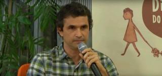 Foto de um homem sentado falando ao microfone.