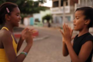 Duas meninas negras brincando de adoleta em uma praça.