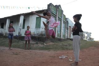 Foto com quatro crianças brincado, três estão brincando de elástico e uma está observando.