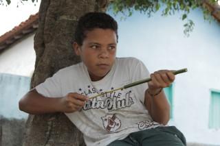Foto de um garoto em baixo de uma arvore, ele está brincando.