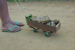 Foto de um caminhão de brinquedo feito de madeira carregando pedras em sua carreta, um garoto puxa o caminhão com uma linha de barbante.