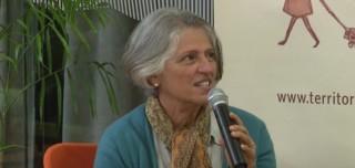 Foto de uma senhora grisalha sentada fala ao microfone.