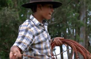 Foto de um garoto com chapéu marrom está girando um corda.