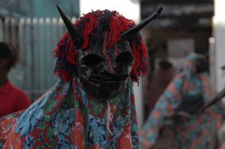 Foto de um bumba meu boi com uma máscara de monstro.