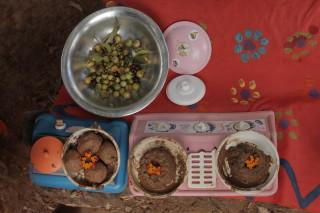 Foto de dois fogões de plástico com pratos de lama, tem uma tigela de alumínio com várias sementes ao lado.