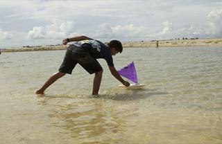 Foto de um garoto em um ribeirão, brinca com um barco a vela de brinquedo.