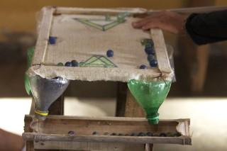 Foto de um brinquedo, mesa de sinuca feita com madeira, bambu e garrafa de plástico, bolinhas de gude estão nela.