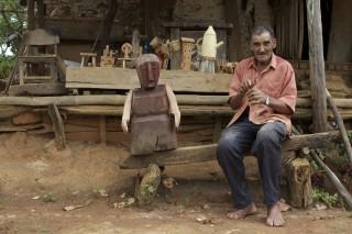 Foto de um senhor sentado em um banco de madeira feito a mão, ao lado direito dele há uma escultura de madeira feita artesanalmente.