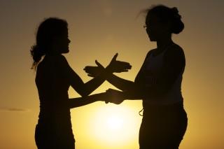 Foto de silhueta de duas meninas brincando de adoleta ao pôr do sol.