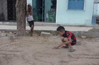 Foto onde uma criança brinca com uma tampinha de garrafa no chão de terra, enquanto outra observa apoiada em uma arvore usa uma máscara e segura um graveto de madeira.