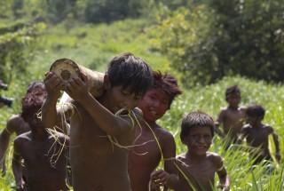 Foto composta por vários garotos carregando tronco e andando em meio ao mato.