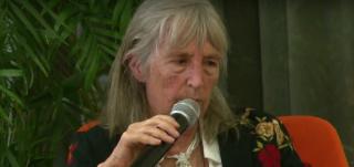 Foto de uma idosa grisalha falando ao microfone.