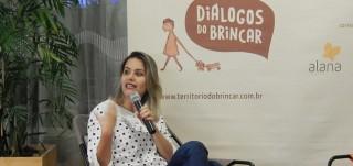 Foto de uma mulher sentada, com suas pernas cruzadas, fala ao microfone.