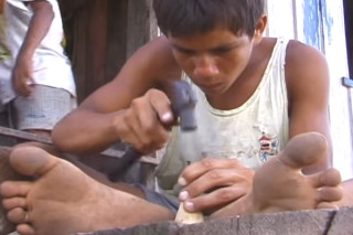 Foto de um menino descalço martelando com um prego a base de um peão de brinquedo.