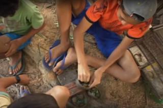 Foto de quatro crianças sentadas em círculo em um chão de terra, o primeiro garoto veste uma camisa laranja e um boné cinza está separando pedras dentro de uma tigela em cima de uma pedra, a sua esquerda um garoto está de lado para a roda o último observa o garoto de camisa laranja.