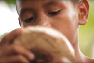 Foto de um garoto segurando e observando uma talha de madeira.